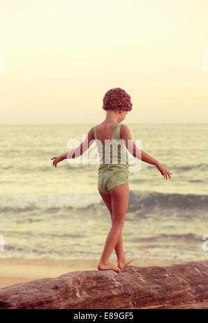 La ragazza di swimcap camminando lungo oceanside rocce Immagini Stock