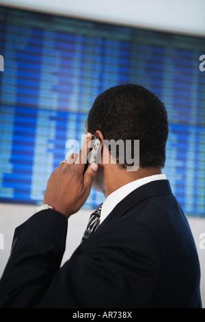 Imprenditore africana guardando Arrivo Partenza board Immagini Stock
