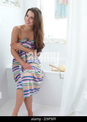 Giovane donna in bagno applicare una lozione Immagini Stock