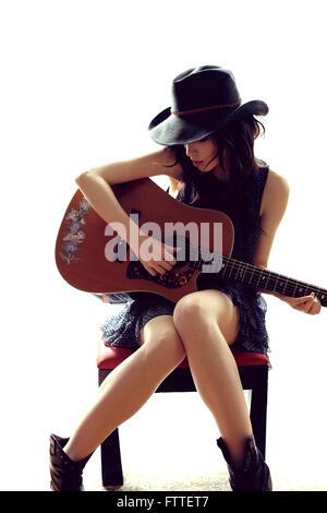 Brunette donna seduta, suonare la chitarra Immagini Stock