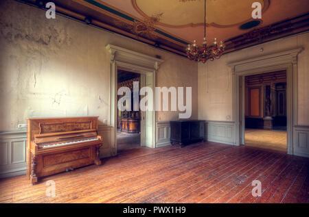 Vista interna di una camera con un pianoforte in una villa abbandonata in Germania. Immagini Stock
