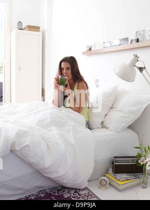 Bruna giovane donna bere il tè a letto Immagini Stock