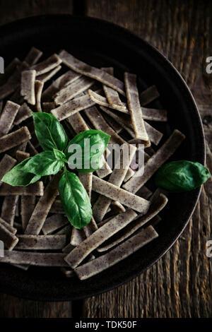 PASTA DI GRANO SARACENO con basilico su un tavolo di legno Immagini Stock