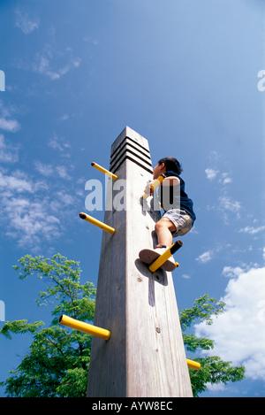 Ragazzo a scalare una delle attrezzature da gioco nel parco Immagini Stock