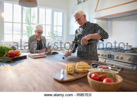 Coppia senior di bere vino in cucina Immagini Stock