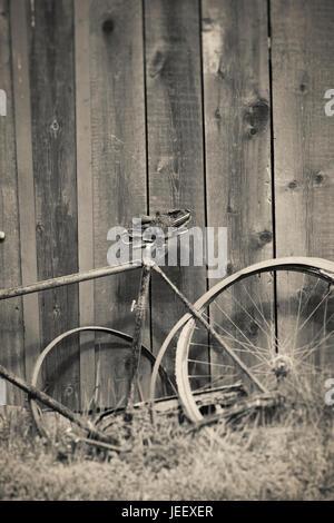 Vecchio rotto bicicletta vintage e pareti in legno. Ancora rurale vita. Immagini Stock