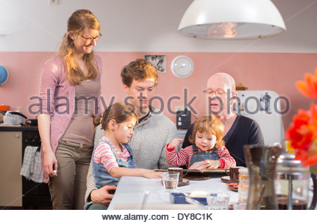 Famiglia ascoltando nonno leggendo ad alta voce un libro per bambini Immagini Stock