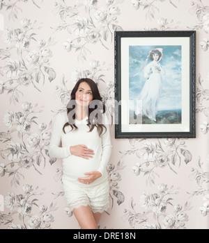 Donna incinta nella parte anteriore della parete floreale Immagini Stock
