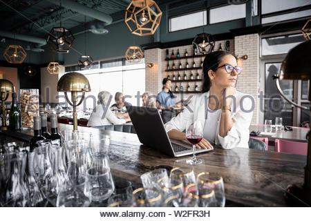 Riflessivo imprenditrice lavora al computer portatile in wine bar Immagini Stock