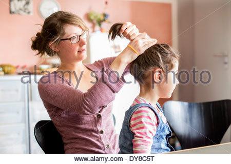 Giovane madre rendendo la figlia una coda di cavallo Immagini Stock