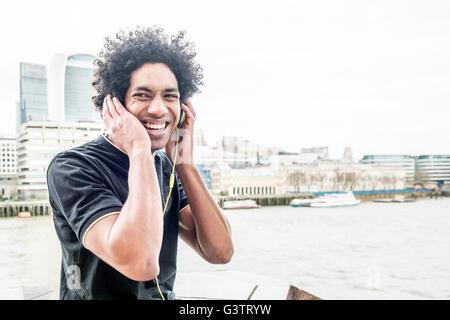 Un giovane uomo che ascolta la musica attraverso le cuffie sulla South Bank di Londra. Immagini Stock