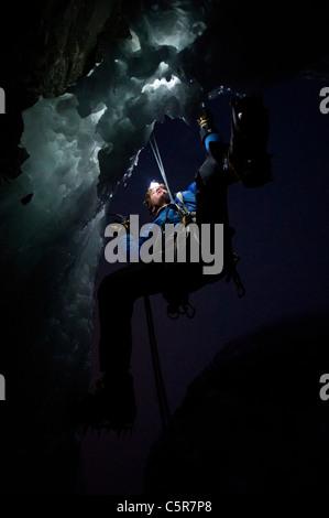 Arrampicata su ghiaccio di notte sul bordo di una grotta. Immagini Stock