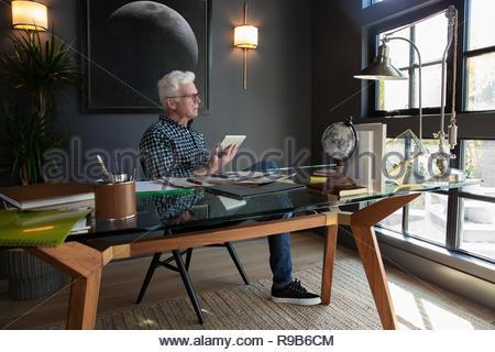 Riflessivo uomo senior con tavoletta digitale in modern home office Immagini Stock