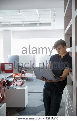 Uomo d affari con computer portatile in ufficio Immagini Stock