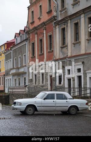 Vecchia volga bianco auto parcheggiata su una strada laterale di ciottoli in kamianets-podilskyi, Ucraina occidentale. Immagini Stock