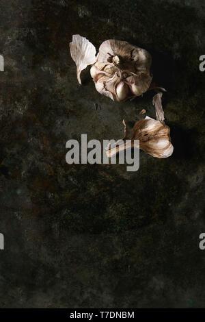 Fresche biologiche bulbi di aglio chiodi di garofano interi e pelati su metallo scuro dello sfondo. Laici piana, spazio Immagini Stock